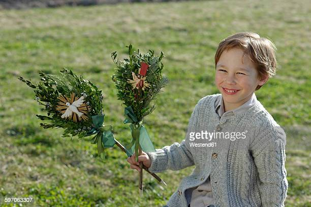 germany, upper bavaria, portrait of smiling little boy with palmbusch on a meadow - palm sunday stock pictures, royalty-free photos & images