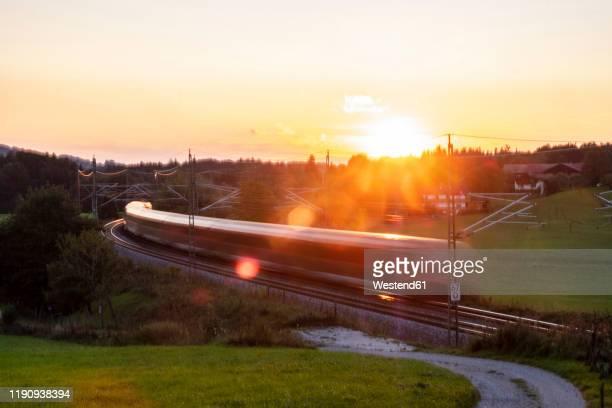 germany, upper bavaria, regional train at sunset - schienenverkehr stock-fotos und bilder