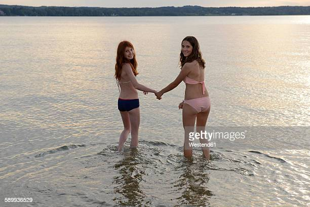 Germany, Upper Bavaria, two girls wading hand in hand in the water of Lake Starnberg
