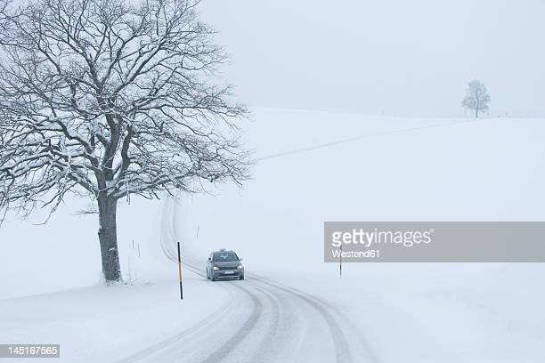Germany, Upper Bavaria, View of car on snowy road