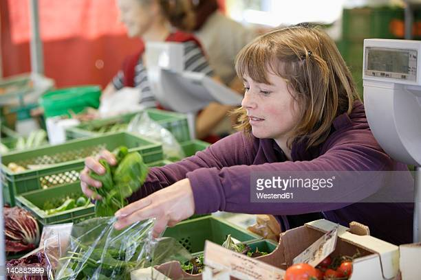 Germany, Upper Bavaria, Wolfratshausen, Woman buying vegetables from market