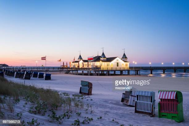 Germany, Usedom, Ahlbeck, view to lighted sea bridge with hooded beach chairs in the foreground at dusk