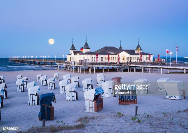 Germany, Usedom, Ahlbeck, view to sea bridge with hooded beach chairs in the foreground at dusk
