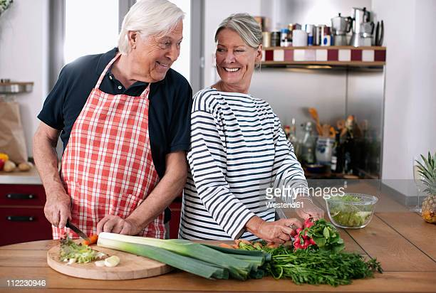 Germany, Wakendorf, Senior couple cutting vegetables in the kitchen