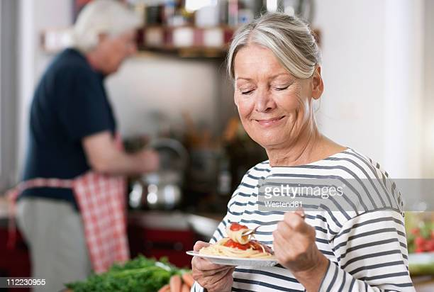 Germany, Wakendorf, Senior woman eating noodle, man cooking in background