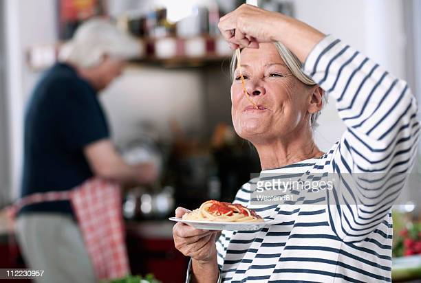 germany, wakendorf, senior woman eating noodles, man cooking in background - man eating woman out - fotografias e filmes do acervo