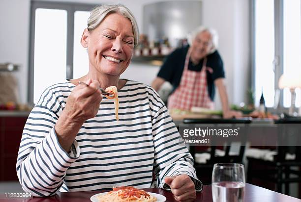 Germany, Wakendorf, Senior woman eating noodles, man cooking in background
