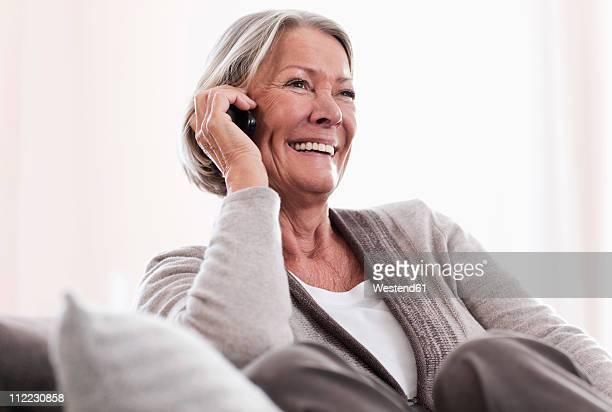 Germany, Wakendorf, Senior woman on the phone, smiling
