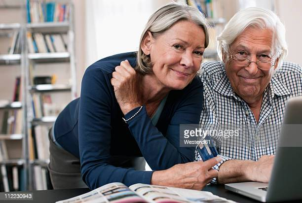 Germany, Wakendorf, Senior  woman with credit card and man using laptop