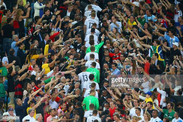 Germany walk through the fans to be presented with their medals and the World Cup trophy after defeating Argentina 10 in extra time during the 2014...