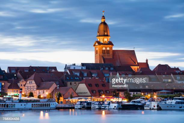 Germany, Waren, view to Mueritz, harbour and city at blue hour