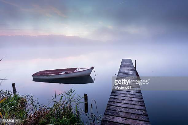 Germany, Wessling, Wesslinger See, boat and wooden boardwalk in the morning mist