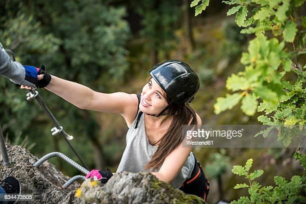 Germany, Westerwald, Hoelderstein, woman climbing on via ferrata