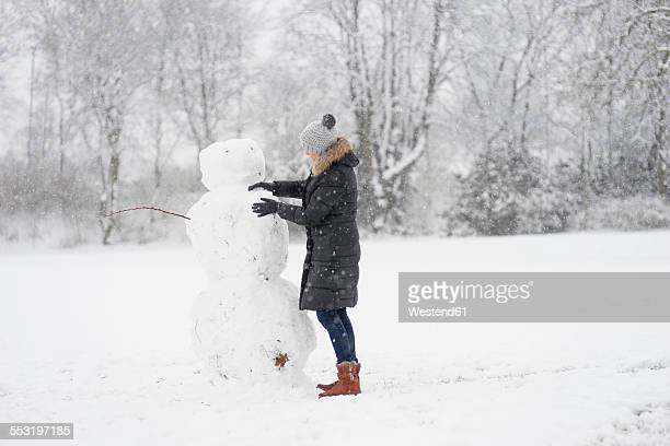 Germany, woman building snowman