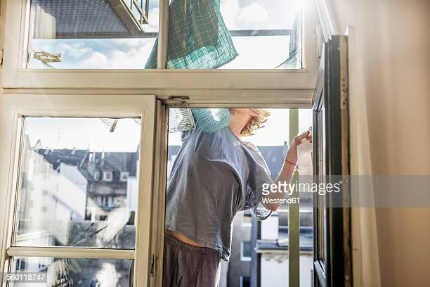 Germany, woman cleaning window at home