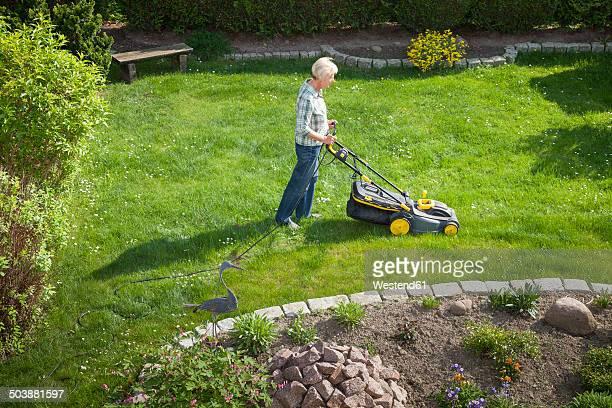 Germany, Woman mowing lawn in garden