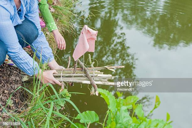 Germany, Woman putting toy raft in water
