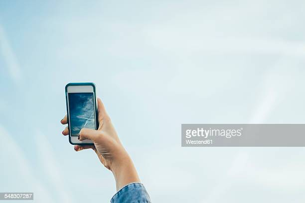Germany, woman shooting to sky with a smartphone