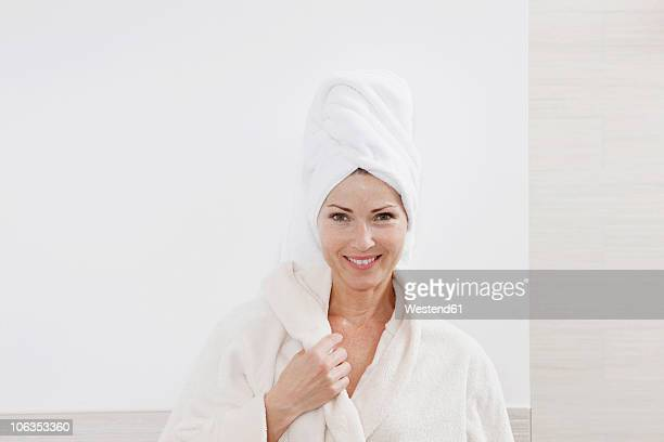 Germany, Woman with bathrobe in bathroom, smiling, portrait