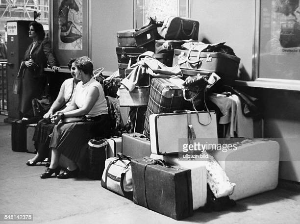Germany Women are chatting next to a pile of suitcases
