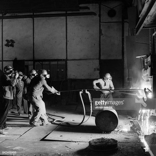 Germany Workers in front of an electric arc furnace preparing the melt for the cast 1960