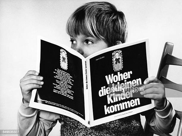 Germany young boy reading a sex education book about 1965