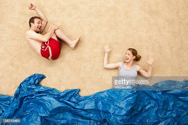 Germany, Young couple enjoying in water at beach