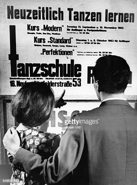 Young couple reading the poster of a dance school early 1960's