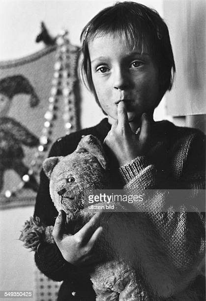 Germany young girl five years old with teddy bear in her arms and finger in her mouth