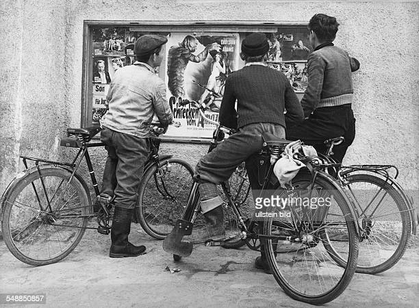 Germany young men with bycicles watching film posters