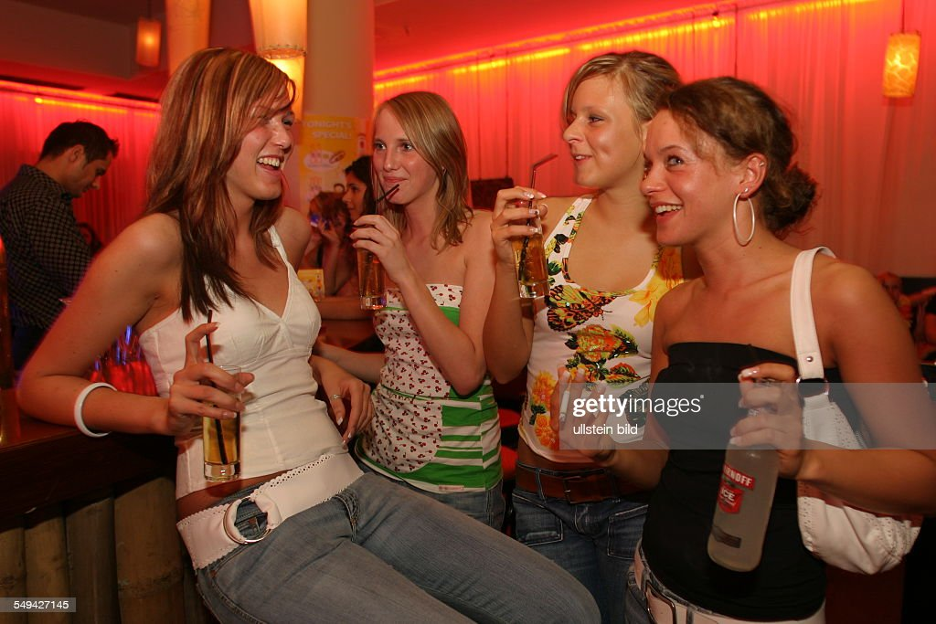 DEU, Germany: Young persons at nightlife.- Four friends at the bar; alcoholic mixed drinks. : News Photo
