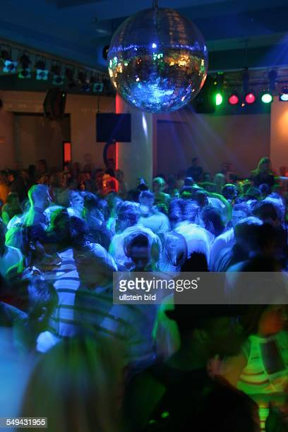 Young persons at nightlife on the dancefloor of a discotheque