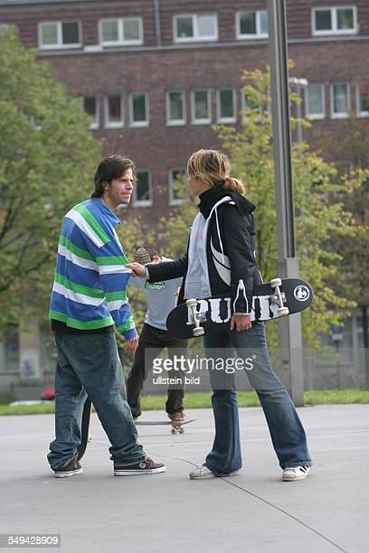 Young persons in their free time Friends skateboarding discussion between a young couple