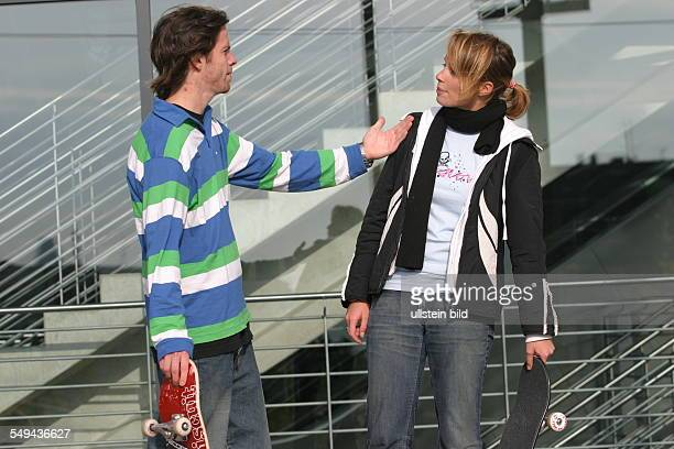 Young persons in their free time Skateboarding discussion between a young couple