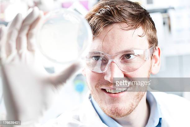 Germany, Young scientist checking petri desh, smiling