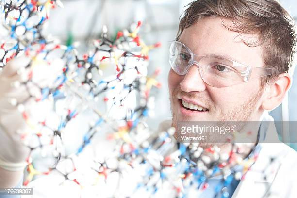 Germany, Young scientist with DNA model