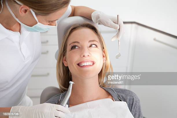 germany, young woman getting her teeth examined by dentist - dental equipment stock pictures, royalty-free photos & images