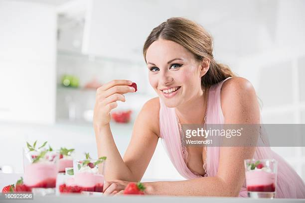 Germany, Young woman holding strawberry, smiling, portrait