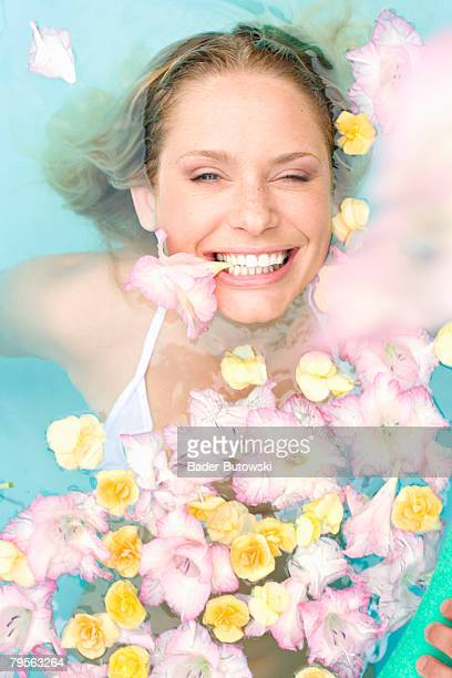 Germany, young woman in pool with flowers, winking, portrait