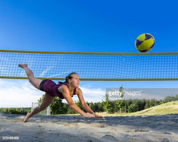 Germany, Young woman playing beach volleyball