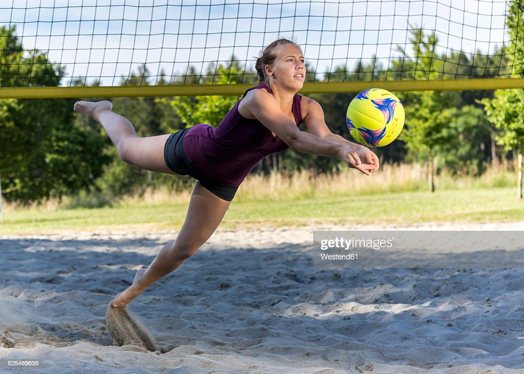 Germany, Young woman playing beach volleyball : Stock Photo