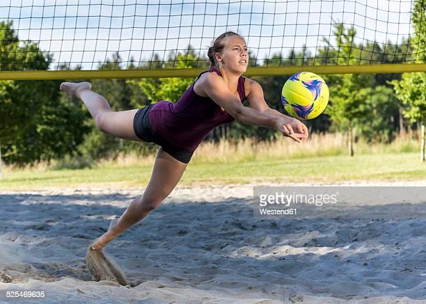 germany, young woman playing beach volleyball - strandvolleyball spielerin stock-fotos und bilder