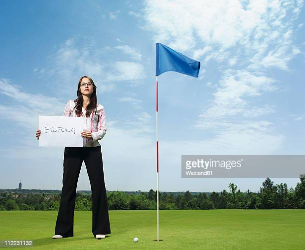 germany, young woman with placard in golf course - golf flag stock photos and pictures