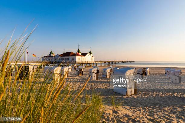 germany,mecklenburg-westernpomerania, ahlbeck, hooded beach chairs on sandy coastal beach with bathhouse in background - ウセドム ストックフォトと画像