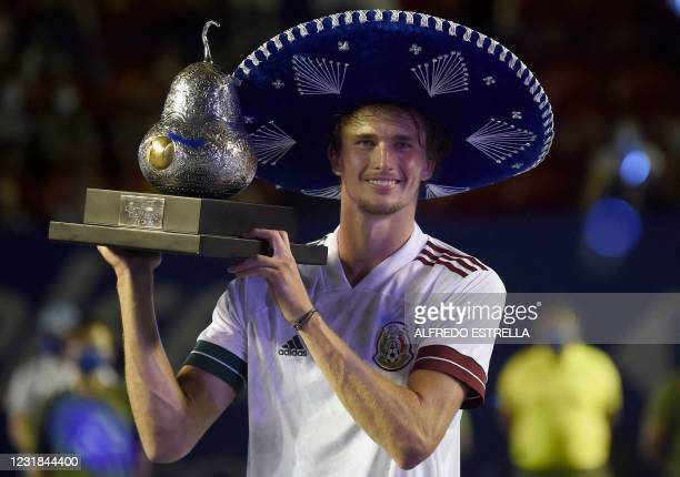 Germany's Alexander Zverev celebrates with the trophy after defeating Greece's Stefanos Tsitsipas and winning Mexico ATP Open 500 men's singles...