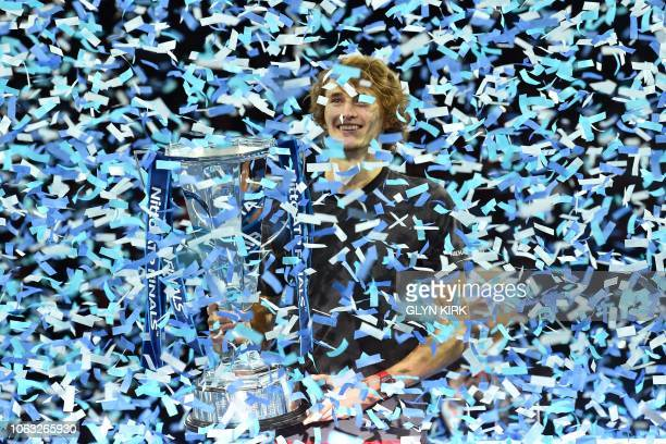 TOPSHOT Germany's Alexander Zverev is covered in ticker tape after being presented with the trophy after beating Serbia's Novak Djokovic in their...