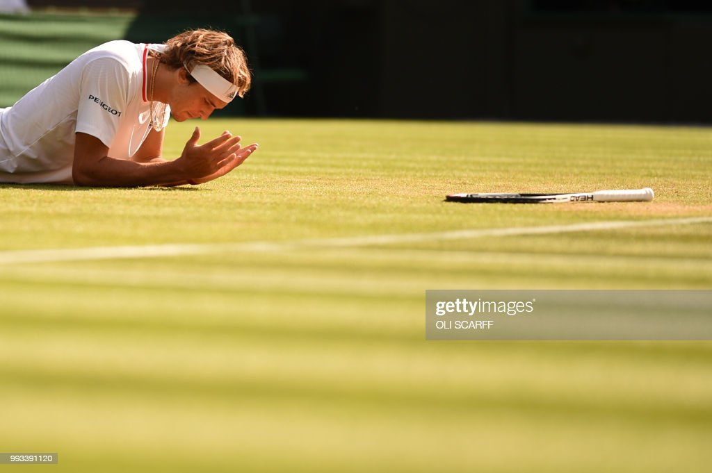 TOPSHOT - Germany's Alexander Zverev slips while playing Latvia's Ernests Gulbis in their men's singles third round match on the sixth day of the 2018 Wimbledon Championships at The All England Lawn Tennis Club in Wimbledon, southwest London, on July 7, 2018. (Photo by Oli SCARFF / AFP) / RESTRICTED