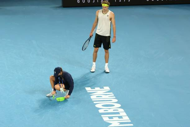 Germany's Alexander Zverev watches as a courtside attendant sweeps the court after Serbia's Novak Djokovic smashed his racquet during their men's...