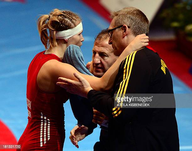 Germany's Aline Focken is helped by staff as she fights against Japan's Sara Dosho during the women's free style 67 kg category for bronze of the...
