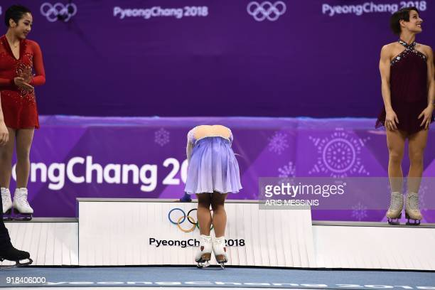 TOPSHOT Germany's Aljona Savchenko reacts on the podium for winning gold with partner Germany's Bruno Massot as silver winner China's Sui Wenjing and...